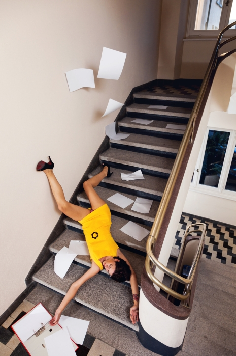 Woman with documents falls down the stairs because of the rush