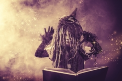 Little girl in a costume of witch casts a spell over magic book. Black-and-white photo.